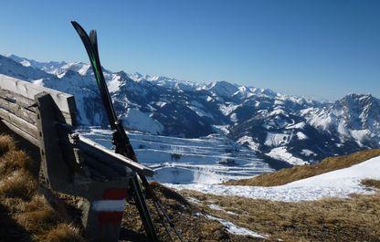 Angelehnte Skier an einer Holzbank mit Blick auf das umliegende Bergpanorama