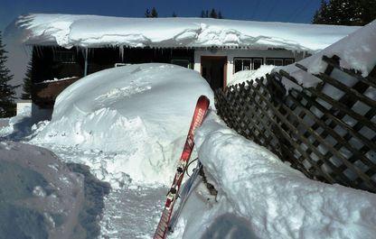 Talstation in schneereichem Winter, mit einem paar Skiern im Vordergrund